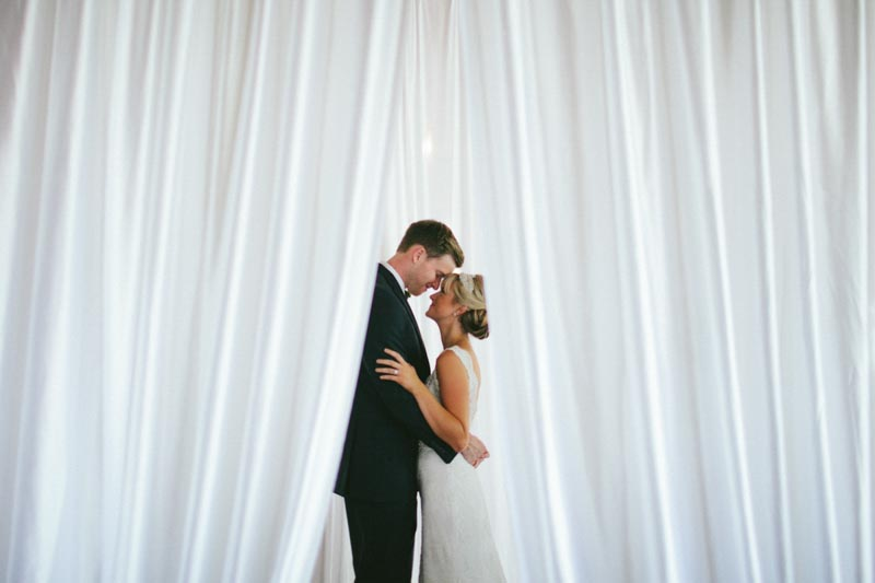 intimate bride and groom white curtains