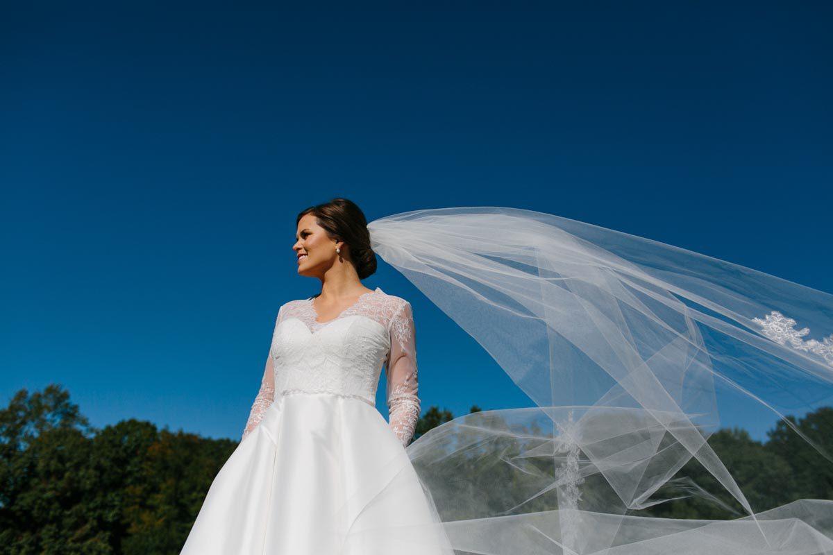 bridal portrait veil flying blue sky bright