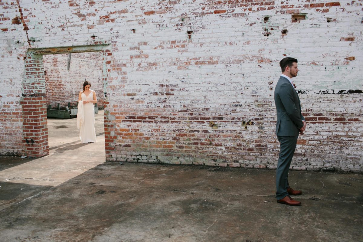 first look brick wall bride and groom
