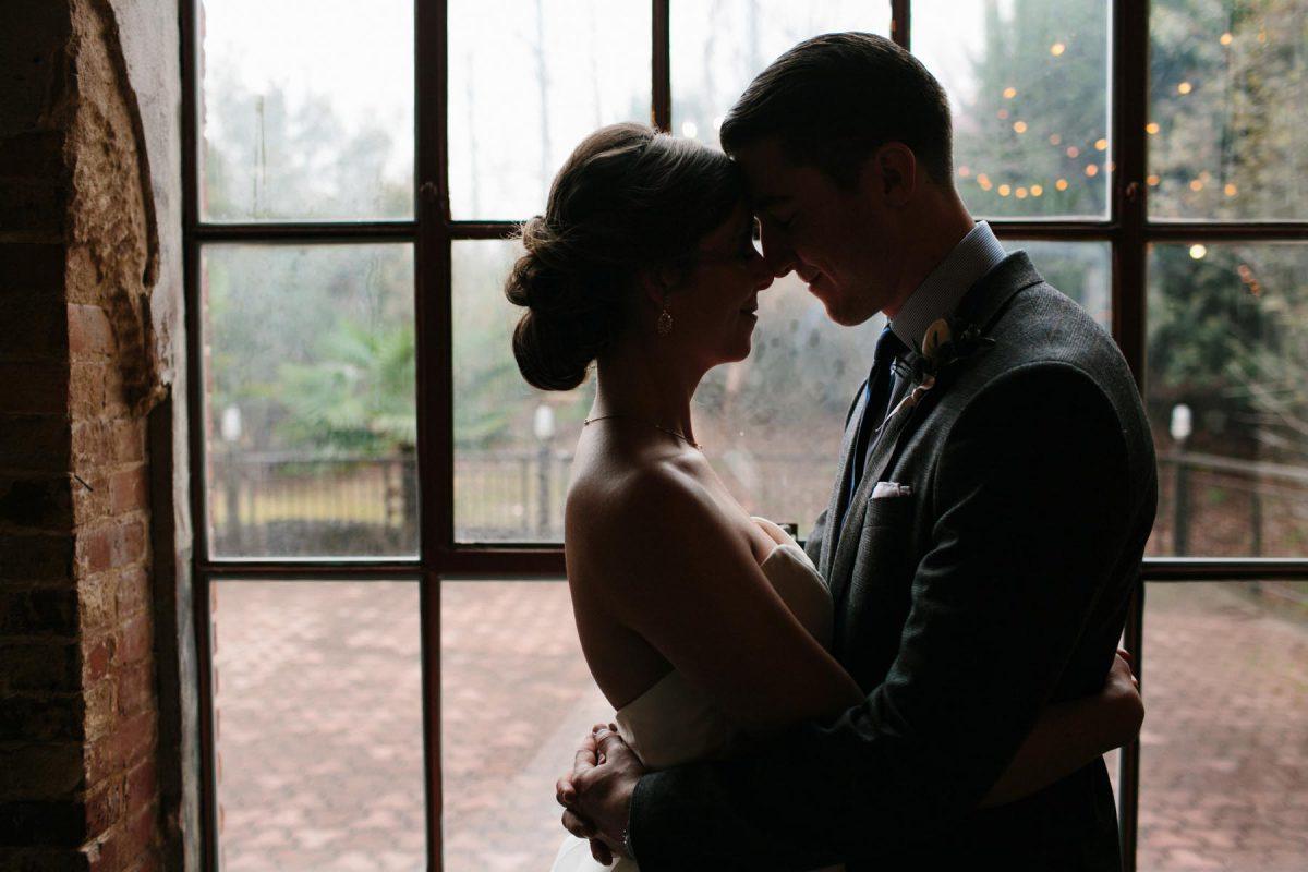 dramatic wedding photo bride and groom window