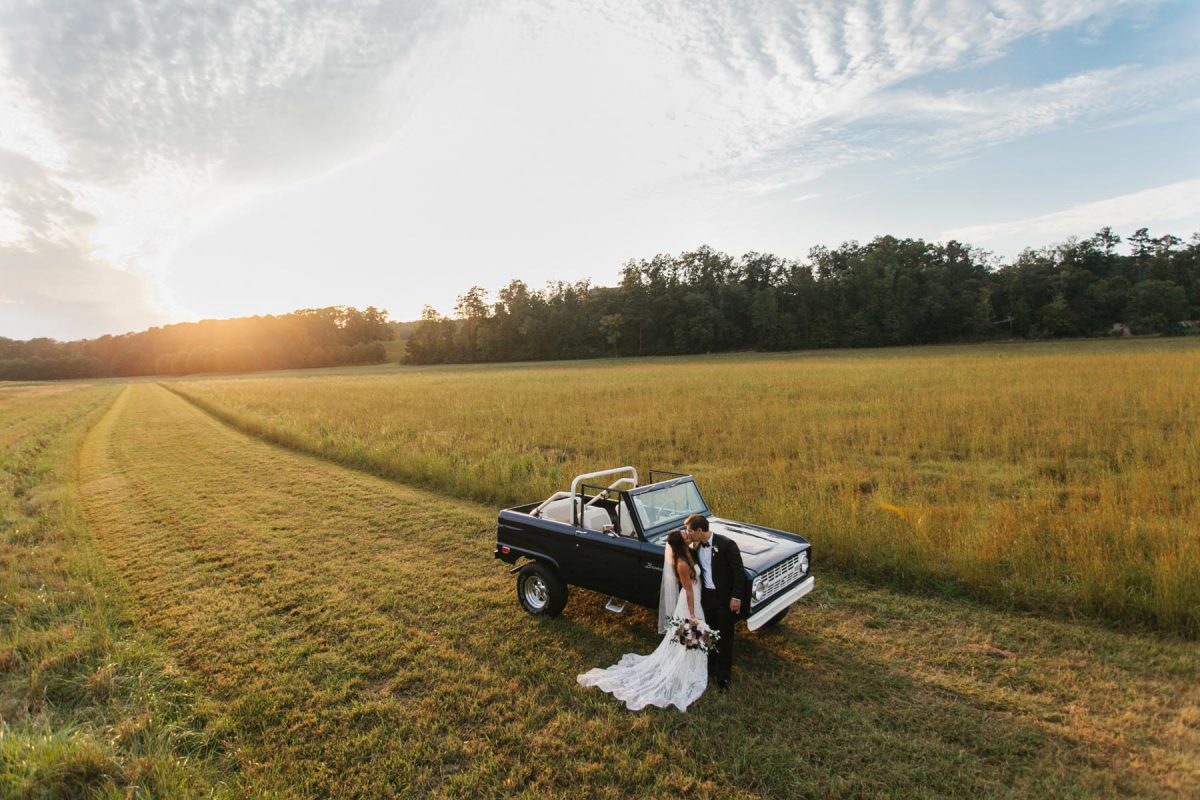 wedding couple at sunset with old bronco