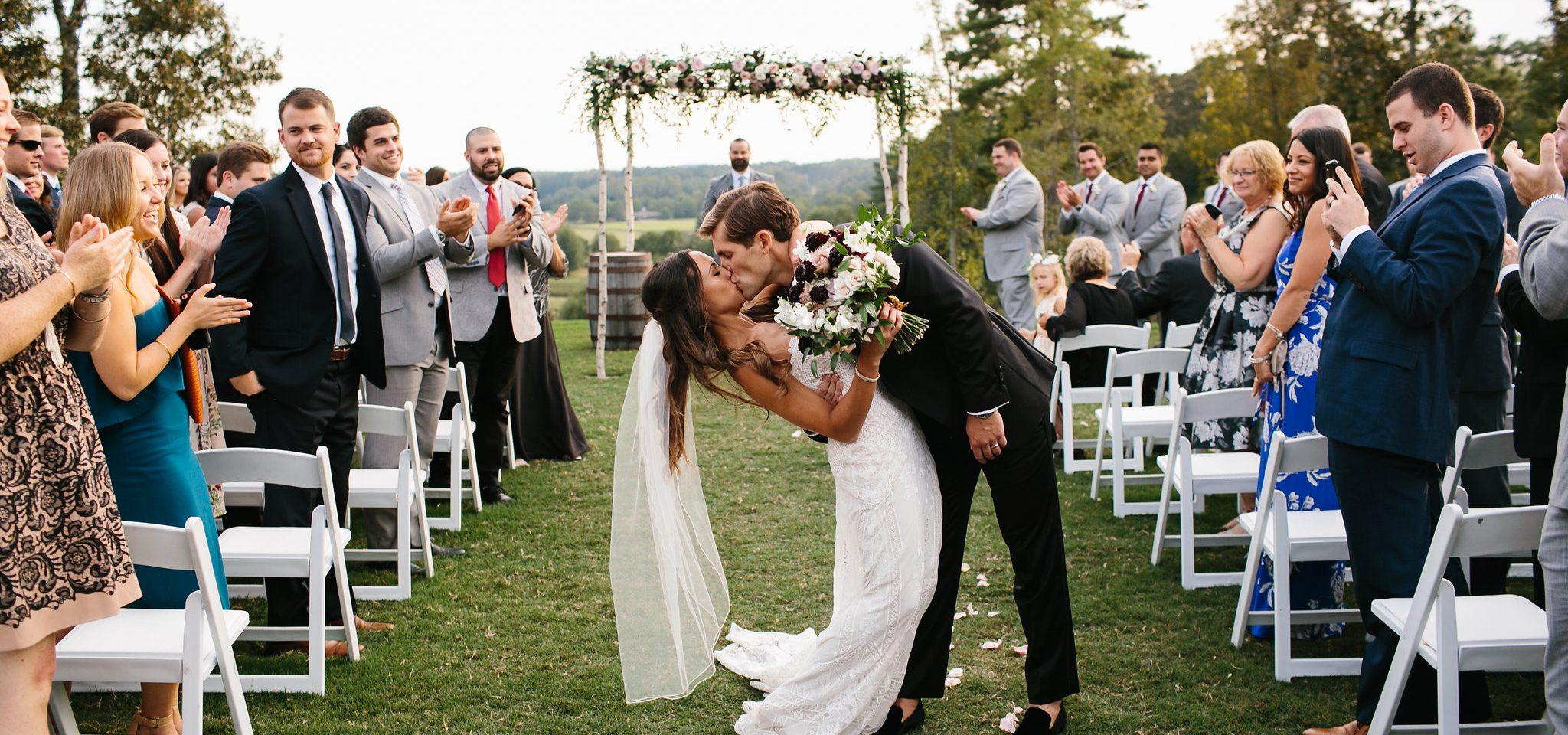 couple leaving ceremony kissing romantic wedding photos
